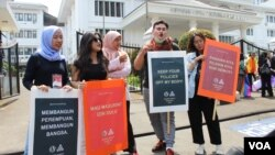 Para peserta aksi Women's March Bandung menyampaikan suaranya di depan gedung DPRD Jawa Barat. Aksi tahun ini fokus menolak eksploitasi anak dan pelecehan seksual. (Foto: Rio Tuasikal/VOA)