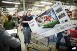 Patrick Bowhay leaves happy from a Wal-Mart store with a Samsung 55-inch television, Nov. 24, 2016.