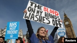 FILE - A junior doctor poses with a banner as she takes part in a demonstration to demand more funding for Britain's National Health Service (NHS), in London, March 4, 2017.