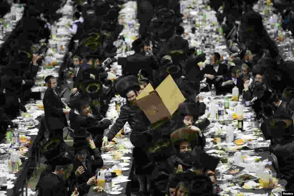 A man distributes fruit from a box at a mass gathering of Satmar Hasidic Jews in New York. The Satmars, a strictly anti-zionist sect of Judaism, gathered to celebrate the 69th anniversary of their founding after Rabbi Joel Teitelbaum's escape from the holocaust.