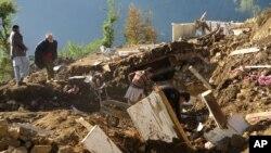 Pobladores paquistaníes de la aldea de Shangla, en el valle de Swat, recogen sus pertenencias de entre los escombros de sus casas destruidas por un terremoto, el lunes 26 de octubre de 2015.