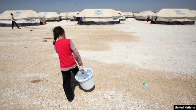 A Syrian girl carries a bucket filled with bottles of precious water to her family's tent in Jordan's al Za'atri refugee camp, September 04, 2012. (UNHCR)