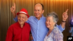 Juris, left, and Lois Greste, parents of Australian journalist Peter Greste, and his brother Andrew, center, pose for the media at a press conference in Brisbane, Australia, Monday, Feb. 2, 2015.
