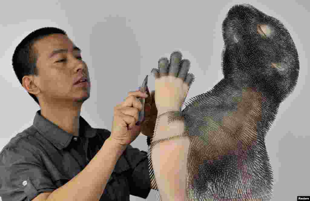 Professor Xie Yong works on an art installation of a beaver, which is made out of plastic and around 300,000 needles, in Shenyang, Liaoning province, China. The needles, according to Xie, represent the pain felt by animals when their fur is taken off to produce clothing.