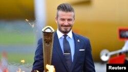 David Beckham saat menyalakan obor olimpiade musim panas di London Inggris Mei tahun 2012 lalu (foto: dok). Kota Sochi, Rusia menjadi tuan rumah olimpiade musim dingin 2014.