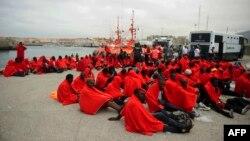 Des migrants sauvés au large de la côte espagnole, sont assis à même le sol au port de Tarifa, 11 Août, 2014.