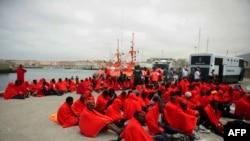 Les immigrants potentiels assis à même le sol au port de Tarifa après avoir été secourus à la côte espagnole, dans le Gibraltar, le 11 août 2014