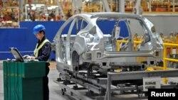 中国汽车制造商协会表示,由于冠状病毒的流行,今年上半年中国的汽车销量可能下滑10%以上。图为2012年4月20日,在重庆市福特汽车制造厂的生产线上,一名员工在旁使用笔记本电脑。(路透社资料照)