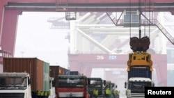 在中国青岛港,工人用吊车把集装箱吊起来装船(2015年10月13日)