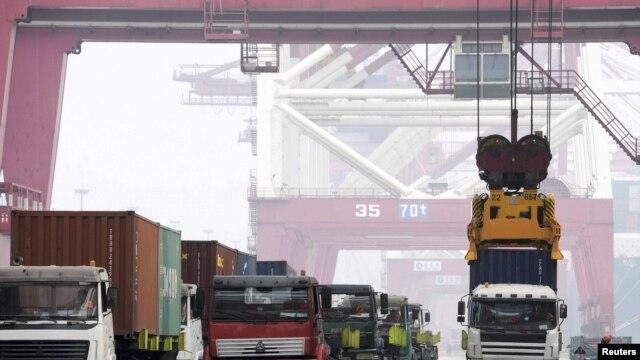 在中國青島港,工人用吊車把集裝箱吊起來裝船(2015年10月13日)