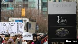 Des manifestants tiennent des pancartes de protestation devant l'hôtel Trump à Vancouver, Canada, le 28 février 2017.