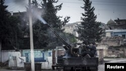 A Free Syrian Army fighter fires an anti-aircraft artillery weapon during an air strike in Binsh near Idlib, December 23, 2012.