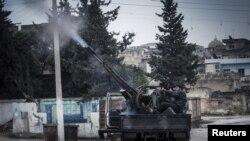 一名叙利亚自由军战士2012年12月23日在叙利亚政府军在伊德利卜附近发动空袭行动时候,使用高射炮向政府军战机开火