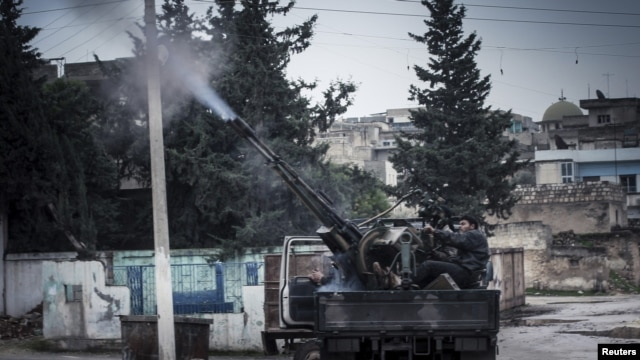 A Free Syrian Army fighter fires an anti-aircraft artillery weapon during an air strike in Binsh near Idlib, December 23, 2012.