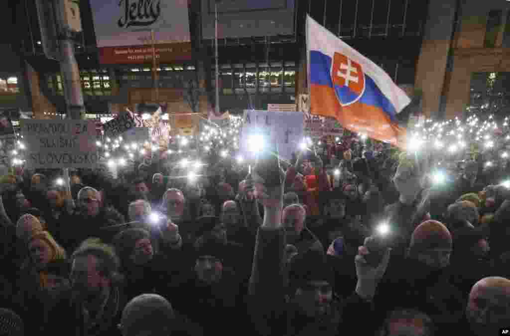 Demonstrators use their smartphones as torches during an anti-government rally in Bratislava, Slovakia, March 9, 2018.
