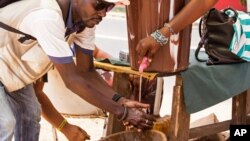 A man washes his hands at a checkpoint in Sierra Leone, as the country enters the third and final day of a three-day countrywide lockdown to combat the Ebola virus in Freetown, March. 29, 2015.