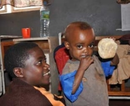 Kefyalew, 3, shows his lunch (right) Markos Ayele, 13, oldest of four orphans