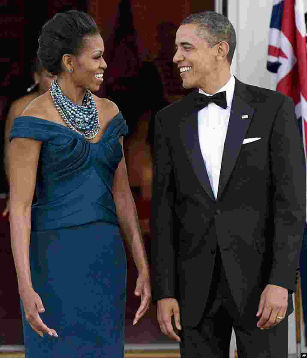 U.S. President Barack Obama and first lady Michelle Obama await the arrival of Britain's Prime Minister David Cameron and his wife, Samantha, for an official dinner in their honor at the White House on March 14, 2012. (Reuters)