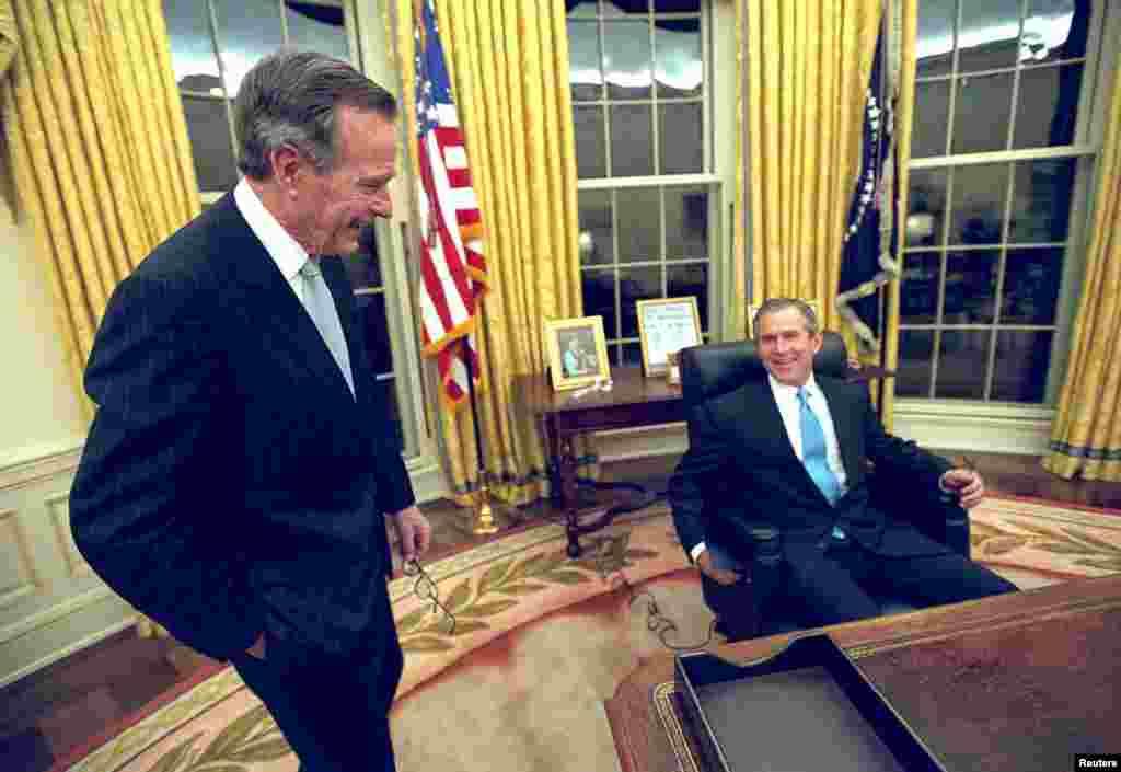 پرزیدنت بوش در نخستین روز ریاست جمهوری در ۲۰ ژانویه ۲۰۰۱ پیش میز کار خود در کاخ سفید نشسته است و پدرش، پرزیدنت جورش هربرت واکر بوش کنار اوست.