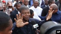 FILE - Joao Lourenco shows his ink-stained finger as he faces the media after casting his vote in elections in Luanda, Angola, Aug. 23, 2017.