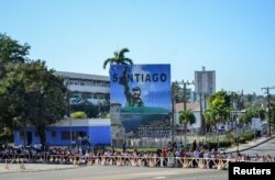 Students wait in line in front of an image of Cuba's late President Fidel Castro before paying tribute to Castro in Santiago de Cuba, Nov. 28, 2016.