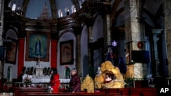 FILE - Chinese women walk past a decoration displaying a Baby Jesus doll part of a Nativity scene, at the Nantang Catholic Church in Beijing. Last month the Chinese government's head of religious affairs told a meeting of the official Catholic Church in the vast Communist country that he hoped the Vatican would try to improve relations by adapting to his society.
