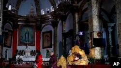Perempuan China berjalan melewati dekorasi Natal di Gereja Katholik Nantang di Beijing. (AP Photo/Andy Wong)