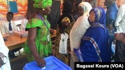 Une Tchadienne remplit les formalités avant d'aller placer son bulletin dans l'urne à côté d'autres électeurs qui attendent dans un bureau de vote à N'Djamena, Tchad, 10 avril 2016. (VOA/Bagassi Koura)