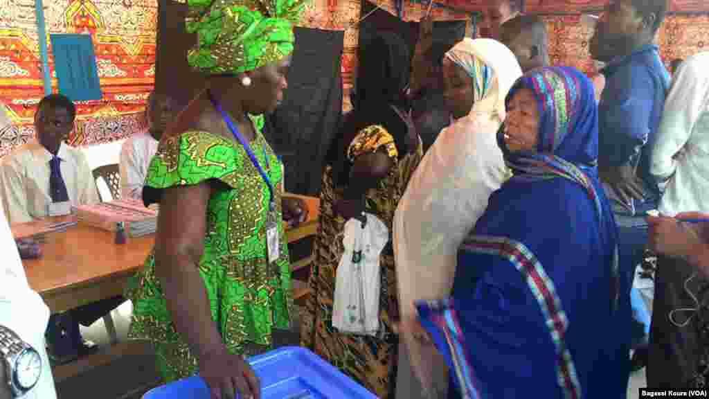 Une Tchadienne se fait aider à placer son bulletin dans l'urne à côté d'autres électeurs qui attendent dans un bureau de vote à N'Djamena, Tchad, 10 avril 2016. (VOA/Bagassi Koura)