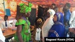 Une Tchadienne remplit les formalités avant d'aller placer son bulletin dans l'urne à côté d'autres électeurs qui attendent dans un bureau de vote à N'Djamena, Tchad, 10 avril 2016. VOA/Bagassi Koura