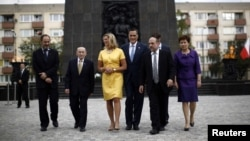 U.S. Republican Presidential candidate Mitt Romney and his wife Ann walk with dignitaries as they visit the monument to the Ghetto Heroes in Warsaw, July 31, 2012.