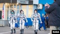 អវកាសយានិកអង្គការណាសារបស់សហរដ្ឋអាមេរិកអ្នកស្រី Kate Rubins (ឆ្វេង) អវកាសយានិករបស់រុស្ស៊ីលោក Sergey Ryzhikov (កណ្ដាល) និងលោក Sergey Kud-Sverchkov (ស្ដាំ) ដើរចេញពីអគារ ២៥៤ ទៅកាន់យានអវកាស Soyuz MS-17 ក្នុងដំណើរទៅកាន់ស្ថានីយ៍អវកាស ថ្ងៃទី១៤ ខែតុលា ឆ្នាំ២០២០។