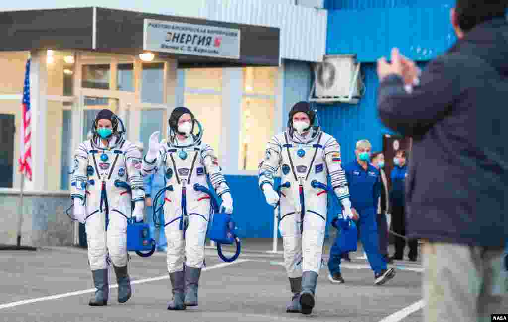 Expedition 64 NASA astronaut Kate Rubins, left, Russian cosmonauts Sergey Ryzhikov, center, and Sergey Kud-Sverchkov, right, depart Building 254 to head to their launch onboard the Soyuz MS-17 spacecraft, at the Baikonur Cosmodrome in Kazakhstan.