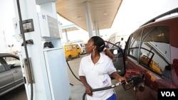 Seorang petugas pom bensin di Lagos mengisi BBM kepada konsumen. Penghapusan subsidi BBM mengakibatkan harga BBM melonjak dua kali lipat lebih dan serikat buruh menyerukan aksi pemogokan.