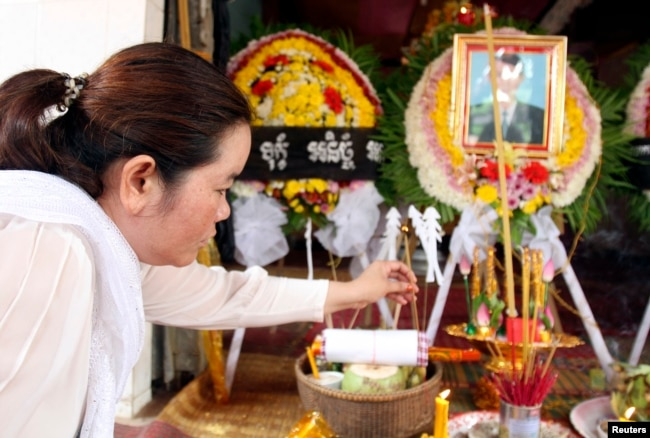 FILE - Sam Chanthy, wife of Chut Wutty, director of the Phnom Penh-based environmental watchdog Natural Resource Protection Group, lights a stick of incense during Wutty's funeral at his house in Kandal province, April 28, 2012.