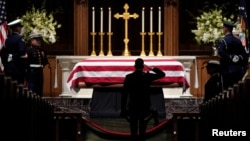 People pay their respects as the flag-draped casket of former President George H.W. Bush lies in repose at St. Martin's Episcopal Church, Dec. 5, 2018, in Houston.