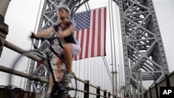 FILE - A bicyclist rides under the largest free-flying American flag in the world, over the George Washington Bridge Monday, Sept. 2, 2013.