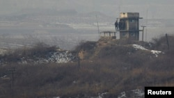 North Korean soldiers watch the South Korean side from a lookout tower at their observation post near the border truce village of Panmunjom in the demilitarized zone (DMZ) separating the two Koreas. South Korea says the sides are removing landmines from the area.