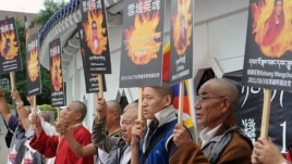 Tibetans display portraits of people who killed themselves in protest of Chinese policies in Tibet, Liberty Square, Taipei, October 19, 2011.