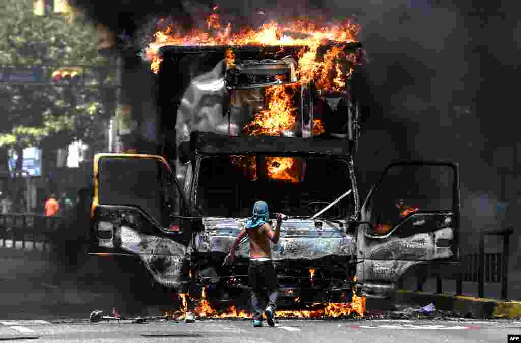 A truck set ablaze by opposition activists blocking an avenue during a protest burns in Caracas, Venezuela.