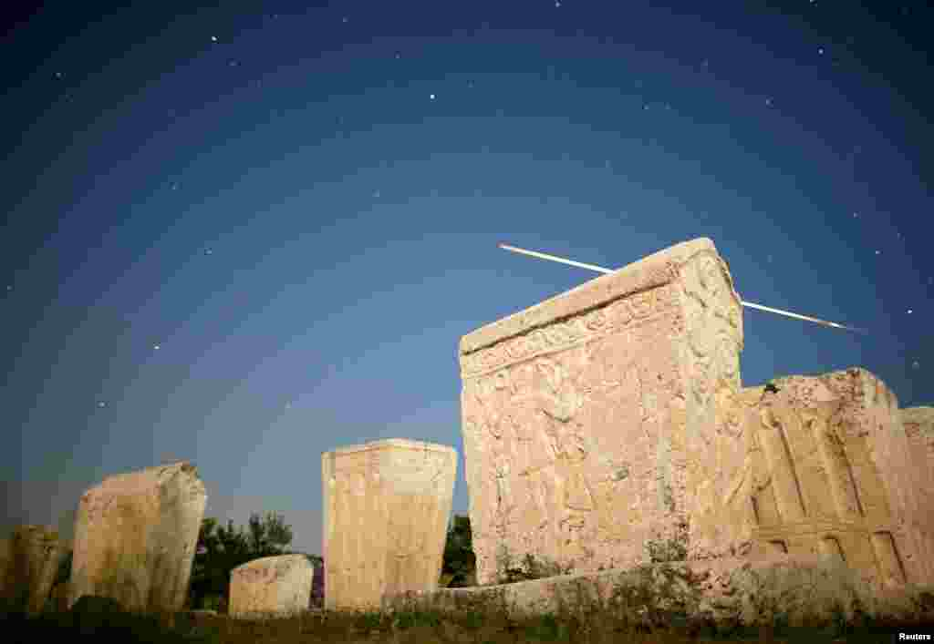 A meteor streaks past stars in the night sky above medieval tombstones during the Perseid meteor shower in Radimlja near Stolac, Bosnia and Herzegovina, Aug. 12, 2019.