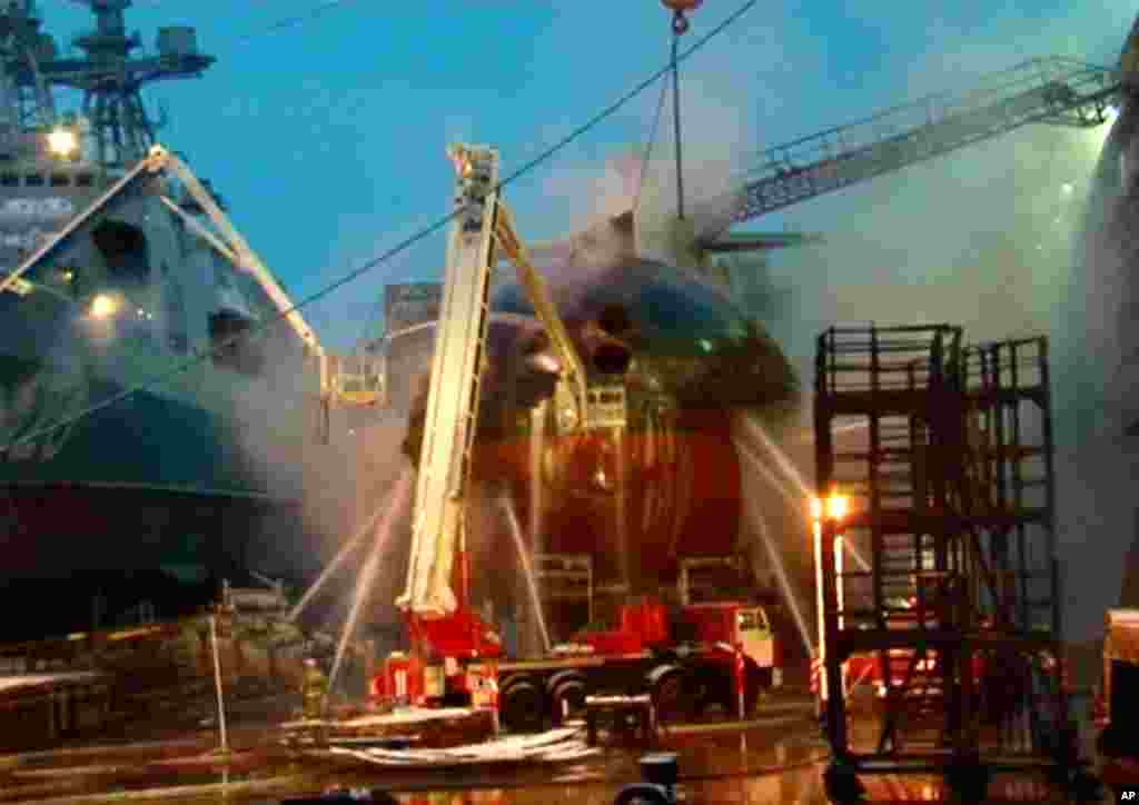 In this video image from Ru-RTR Russian state television channel, firefighters spray water on the Yekaterinburg nuclear submarine in a dock at the Roslyakovo shipyard in the Murmansk region, Russia. (AP Photo)