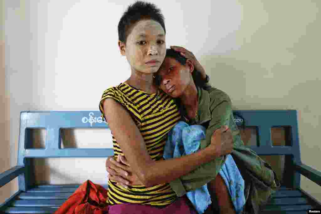 Mye Nyo (R) is comforted by Thidar Win at a Catholic-run hospice for AIDS patients in Myitkyina, the capital of Kachin State, Burma.