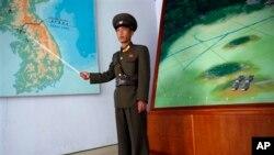 지난해 4월 판문점을 방문한 관광객들에게 비무장지대에 대해 설명하는 북한 병사. (자료사진)