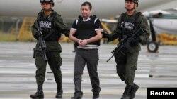 """La policía colombiana escolta al narcotraficante Daniel """"Loco"""" Barrera para abordar el avión de la DEA que lo trasladaría a Nueva York para entregarlo a las autoridades."""