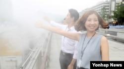 폭염이 이어진 20일 서울 광화문 광장 물 분무 시설 옆에서 시민들이 더위를 식히고 있다.
