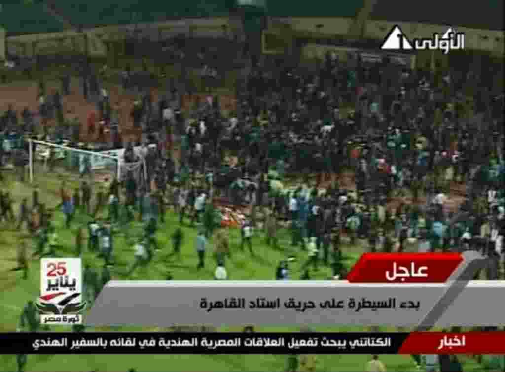 Gambar dari Egypt TV ini memperlihatkan para pendukung bentrok di stadion Port Said, Mesir (1/2) (AP).