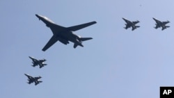 FILE - U.S. B-1 bomber, center, flies over Osan Air Base with U.S. jets in Pyeongtaek, South Korea, Tuesday, Sept. 13, 2016. (AP Photo/Lee Jin-man)