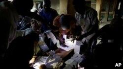 Les responsables électoraux utilisent les torches de leurs téléphones portables pour préparer les bulletins de vote à la fermeture des bureaux de vote à Kaduna, au Nigeria, samedi 28 Mars 2015