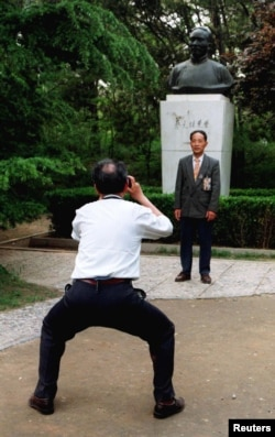 北京大学校友在中国最著名的教育家之一,北京大学前校长蔡元培的塑像前拍摄纪念照。